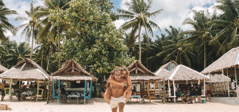 Pareja disfrutando de una playa paradisíaca una vez preparada su mochila para Filipinas